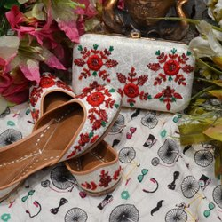 Partywear White Color Punajbi Jutti With Maching Clutch With Red Flower Work.